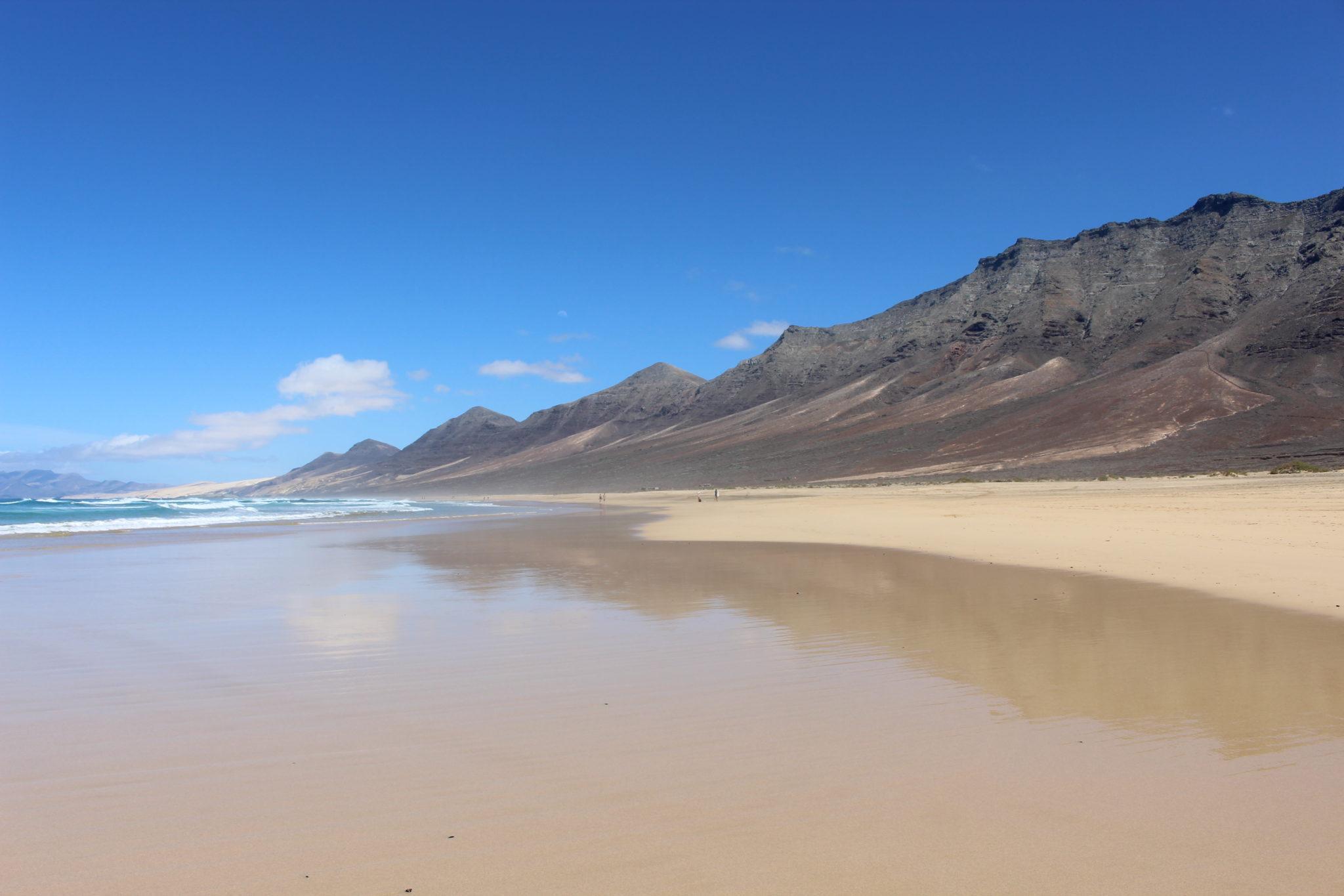 W rozlewającej się po piasku fali pięknie odbijają się otaczające plażę wzgórza.